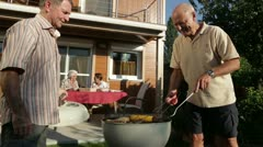 Seniors garden grilling in summer Stock Footage