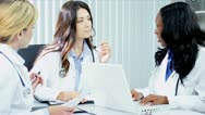 Multi ethnic doctors finishing clinical trials on computers with handshake  Stock Footage