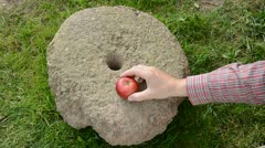 Put three summer end apples on historical millstone Stock Footage