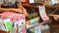 Tourists buying green tea at Asakusa market Stock Footage