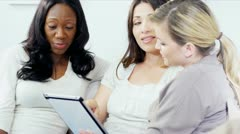 Caucasian and African American women social networking on tablet   Stock Footage