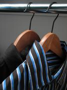 Two stylish shirts on wooden hangers Stock Photos