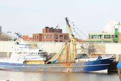 Fishtrawler in a harbor Stock Photos