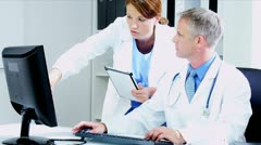 Caucasian Hospital Doctors Updating Patient Information using tablet  Stock Footage