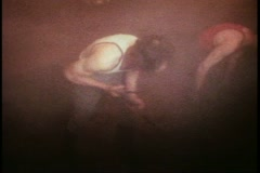 Whitbread brewery, men shovel barley out of vat, London, England, 1970's Stock Footage
