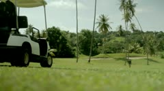 Golf car is driving over a tropical golf course Stock Footage
