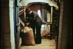 Whitbread brewery, man in suit, digs into barley bag, London, England, 1970's Stock Footage
