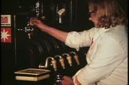George Inn, barmaid pulls handles to draw beer, London, England, 1970's Stock Footage