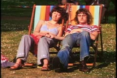 Stock Video Footage of Parks of London, couple in canvas chairs, taps foot to music, London, 1970's
