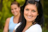 Mother smiling with teen daughter in background Stock Photos