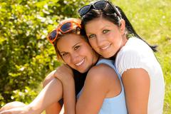 mother and teen daughter hugging outdoors relaxing - stock photo