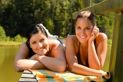 Mother and daughter sunbathing on pier smiling Stock Photos