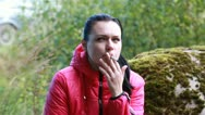 Young woman sitting on a stone and smoke Stock Footage