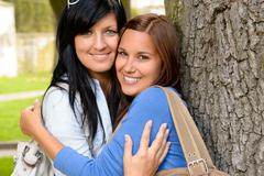 Mother and teen hugging outdoors relaxing smiling Stock Photos