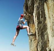 Girl climbing on the rock Stock Photos