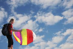 Happy young woman flying a kite Stock Photos