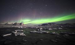 Northern Lights over the frozen Arctic fiord - stock photo