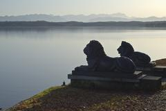a lion statues with german alps - stock photo