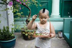 Stock Photo of Saigon in Vietnam. Vietnamese culture,buddhist kid,people,city life, motorbikes.