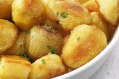 Crunchy roast potatoes and onions Stock Photos