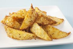Potato wedges with cajun seasoning Stock Photos