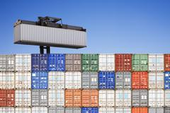 shipping container above stacked others - stock photo
