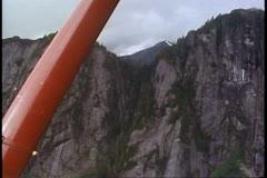 Misty Fjord, air flight, POV passing rocky cliffs, plane strut, Alaska Stock Footage