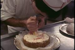 Galley of ship, low, man decorates cake, Alaska Cruise, Island Princess Stock Footage