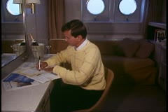 Man in cabin on cruise ship, writing at desk, cleared talent Stock Footage