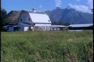 Matanuska Valley, Alaska, barn, mountains in background, fields Stock Footage