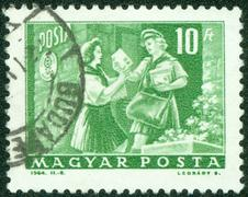 Stamp shows girl pioneer and woman letter carrier, circa 1964 Stock Photos