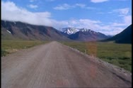 Motor coach on the gravel Dalton Highway, POV gravel road, mountains Stock Footage