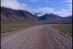 Motor coach on the gravel Dalton Highway, Alaska, POV gravel road Stock Footage