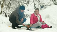 Stock Video Footage of Couple Frying Sausages On Fire In The Winter Forest