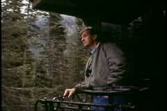 White Pass & Yukon Railroad, Alaska, man stands of rear of car looking out Stock Footage