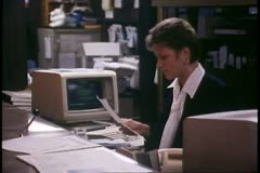 Woman at computer at a hotel desk, circa 1988 - stock footage