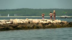 Girls on rocks in bikinis - stock footage