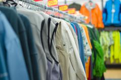 variety of shirts, vests and t-sirts on stands in supermarket - stock photo