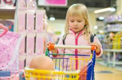 adorble girl with small shopping cart in kids mall - stock photo