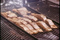 Salmon bake in Alaska on outside, grill, cook bastes salmon on grill Stock Footage