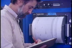 Seismology center, scientist inspects rotating drums, University of Alaska Stock Footage