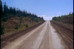 Motor coach, the gravel Dalton Highway, POV gravel road, pass pine trees Stock Footage