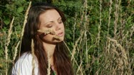 Beautiful girl sits in a high grass Stock Footage