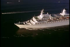 Aerial shot of cruise ship, The Love Boat, sailing out to the open sea Stock Footage