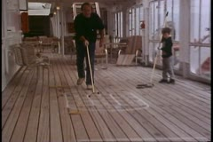 Shuffleboard, close up man, zoom out wide to little boy, cruise ship Stock Footage