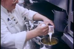 The Alaska Railroad, train galley, staff preparing food, Wisk cream in pot Stock Footage