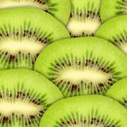 abstract green background with raw kiwi slices - stock photo