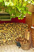 Pergola with grapevine and fire-wood Stock Photos