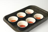 Six pots with caramel in oven tray Stock Photos