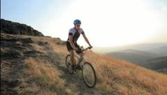 A view of a biker riding a mountain bike on a sunset - stock footage